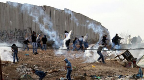 Palestinian demonstrators seeking safe place against tear gas canister fired by Israeli troops during protests against Israel's military operations in Gaza