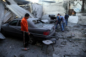Palestinian citizens observe a car near the Islamic National Bank branch, after an Israeli air strike