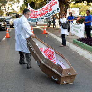 Doctor pulls coffin symbolizing health during protests against the