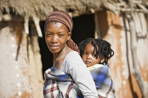 African woman carrying her daughter. The report states that women and girls are especially vulnerable to HIV infection due to a variety of biological and social factors.